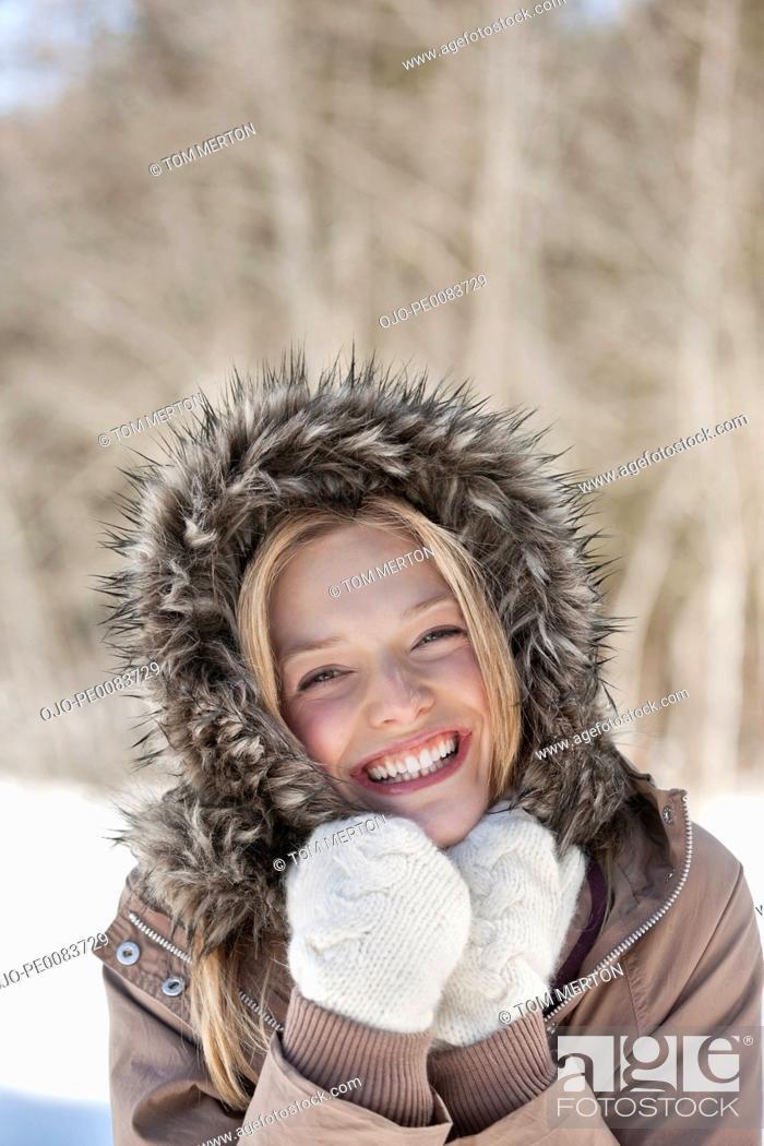 Stock Photo: Portrait of smiling woman wearing fur hood coat.