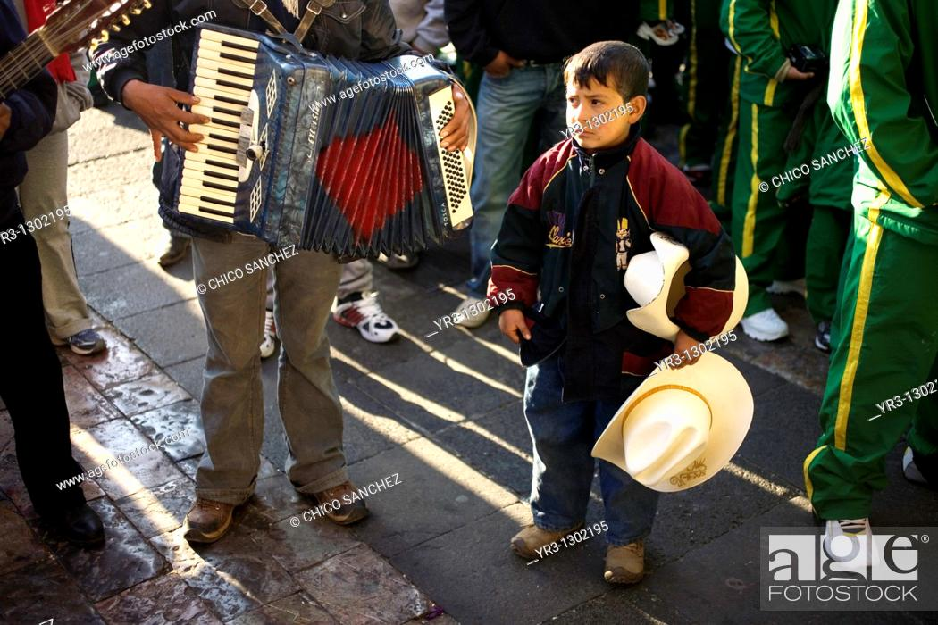 Stock Photo: A boy looks at a musician playing the accordion outside the Our Lady of Guadalupe Basilica in Mexico City, December 10, 2008  Hundreds of thousands of Mexican.