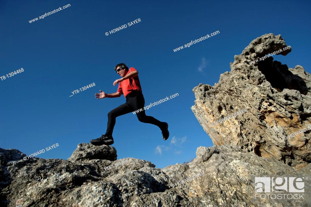 Stock Photo: Man running and jumping over rocky terrain.