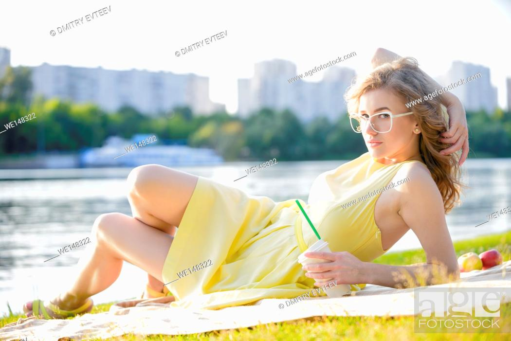 Stock Photo: Woman is getting picnic on a blanket in a city park at pond shore.