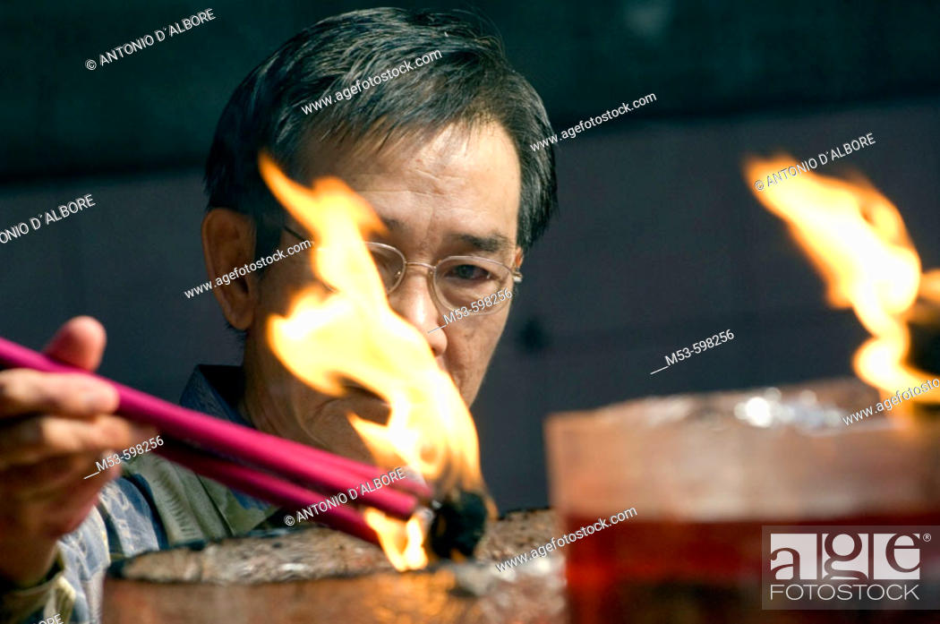 Stock Photo: an indonesian man light up incense sticks in Vihara Dharma Bhakti temple in chinatown. west jakarta. indonesia. asia.