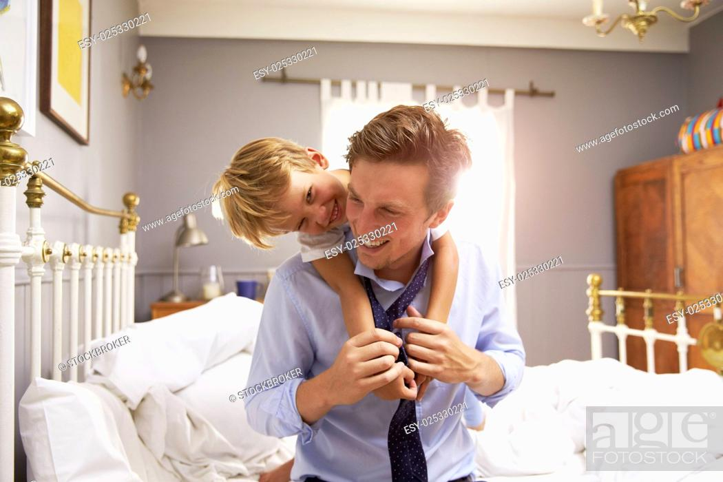 Stock Photo: Son Hugging Father As He Gets Dressed For Work.