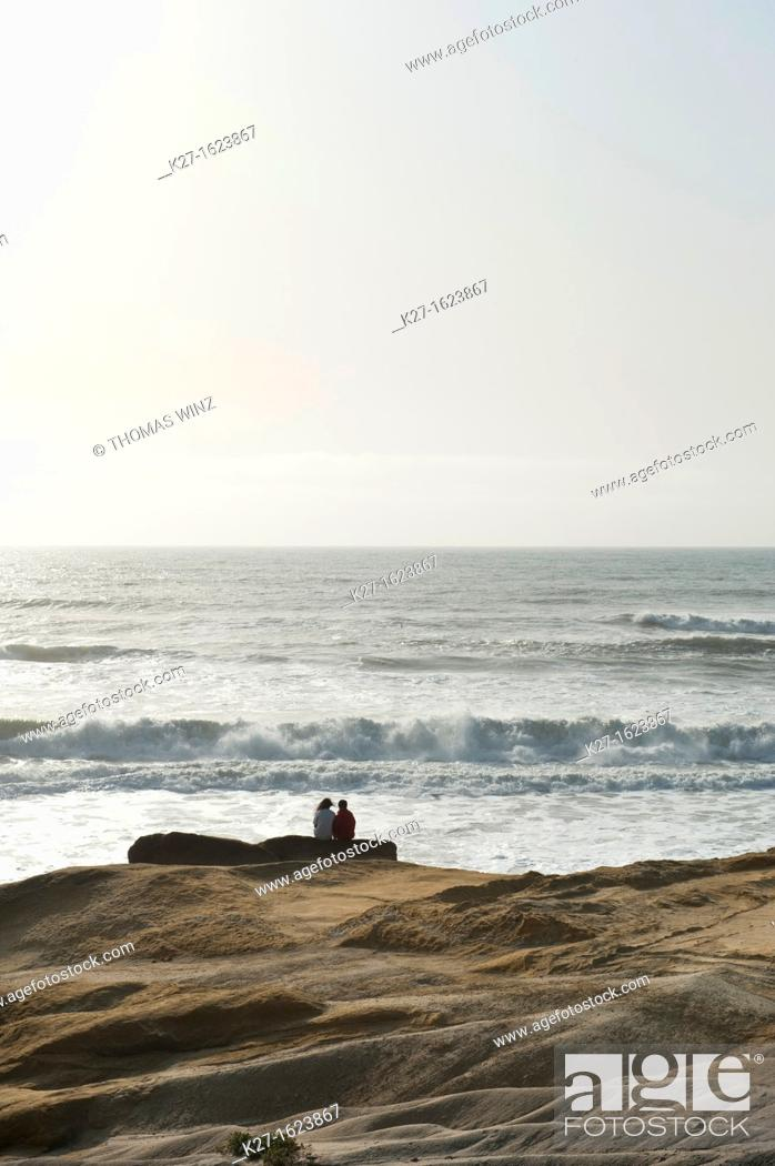 Stock Photo: Two people sitting on a rock watching the waves.