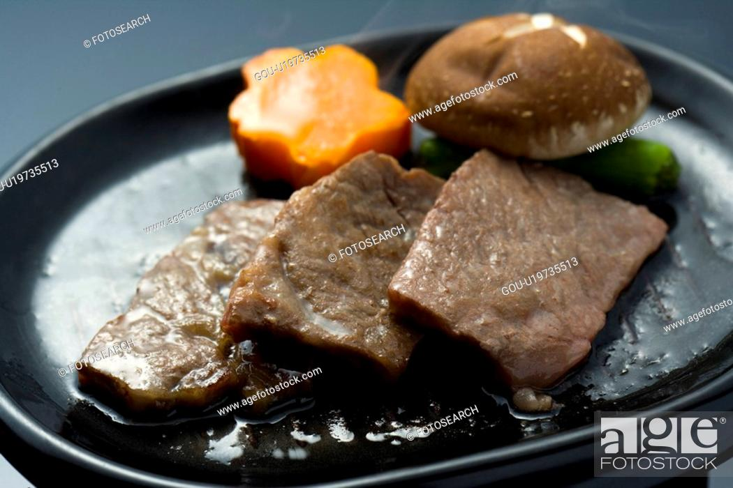 Stock Photo: Slices of grilled beef and vegetables on a plate, high angle view, close up, black background, Japan.
