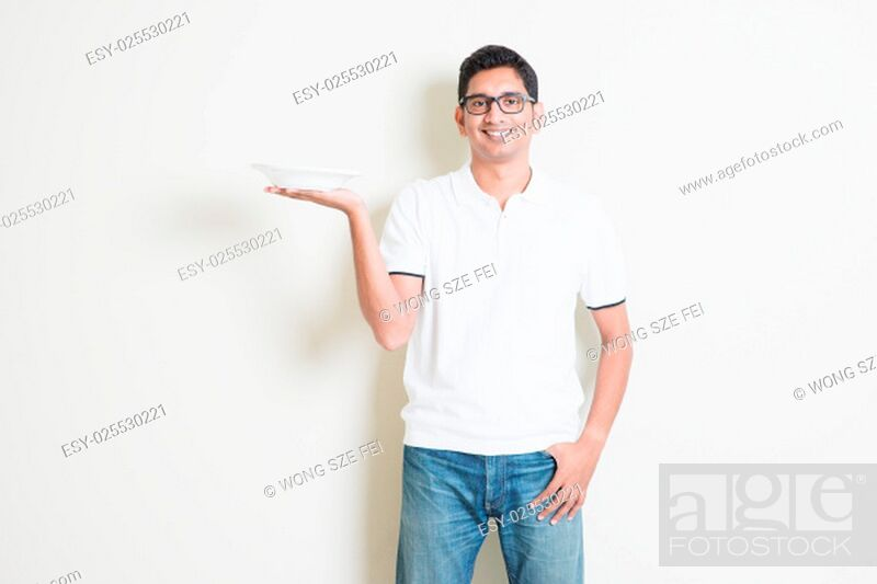 Stock Photo: Dining concept. Indian waiter holding an empty plate on hand, ready for food. Asian man standing on plain background with shadow and copy space.