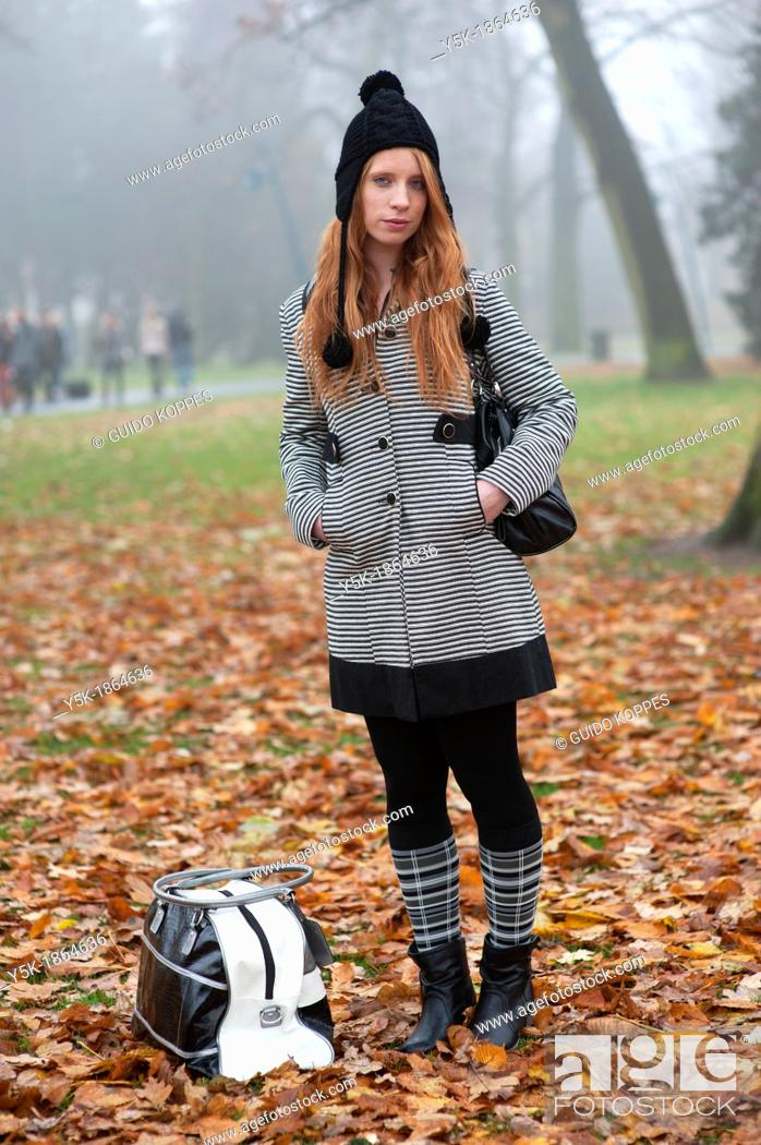 Stock Photo: Breda, Netherlands. Young, fashionable and redheaded woman in a city-park.