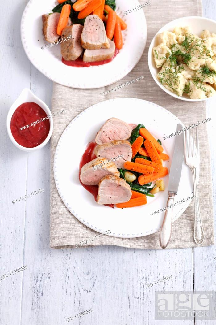 Stock Photo: Pork loin with spinach, carrots, cherry sauce and dill Spätzle (soft egg noodles from Swabia).