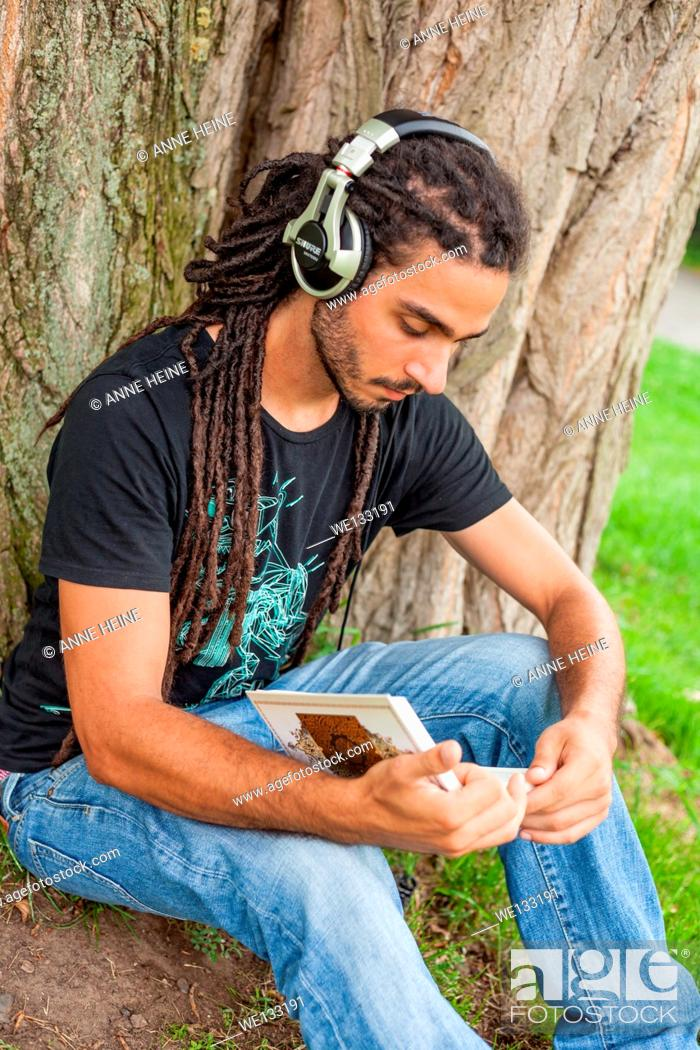 Stock Photo: Man with rasta hair reads a book and listens to music, Germany.