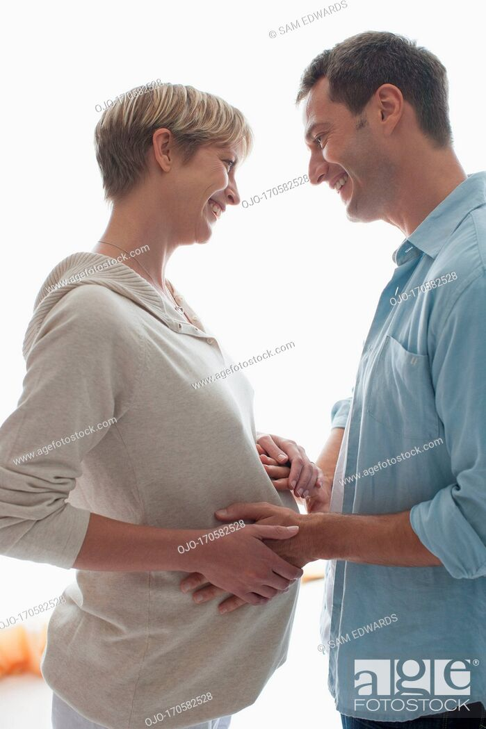 Stock Photo: Husband holding pregnant wife's stomach.