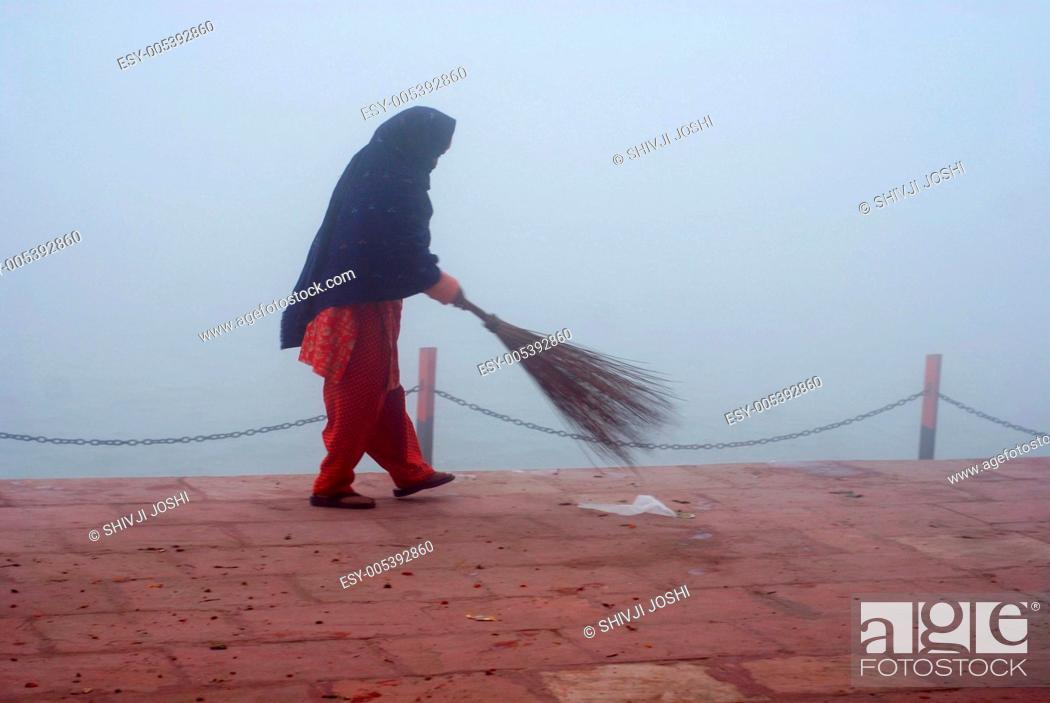 Sweeper cleaning ghat of river ganga ganges , Haridwar