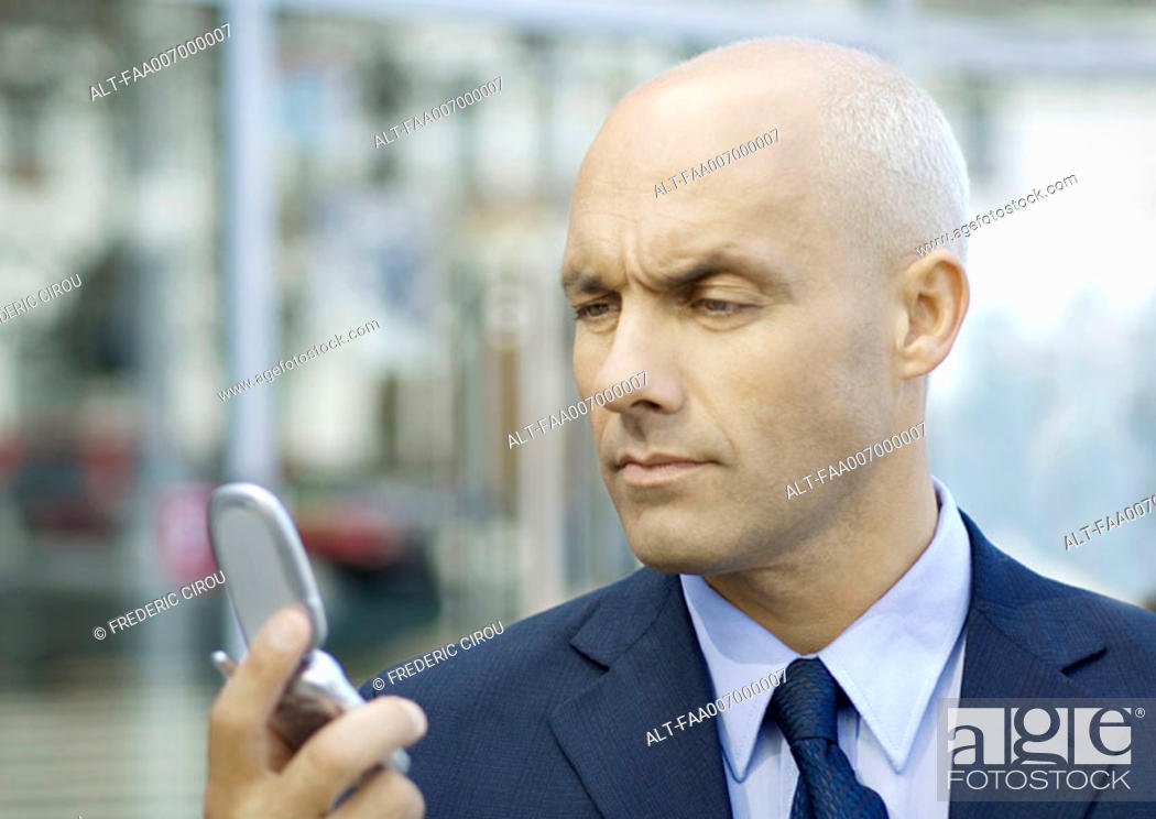 Stock Photo: Businessman looking at cell phone, furrowing brow.