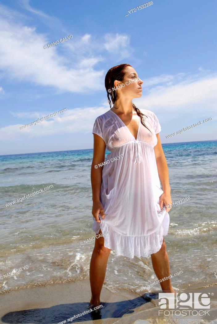 Stock Photo: Sensual and attractive red haired girl on the beach, wearing a wet white dress  Ibiza, Spain.