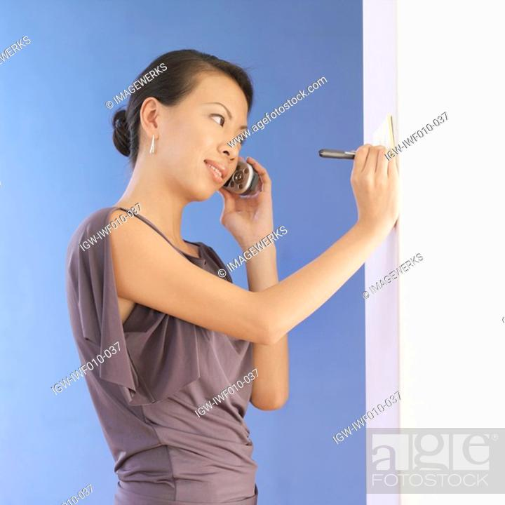 Stock Photo: Side profile of a young woman talking on a mobile phone.