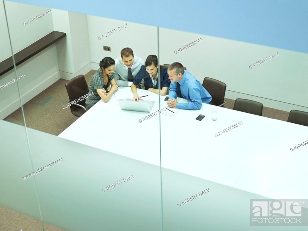 Stock Photo: Four businesspeople at a table with documents and laptop.