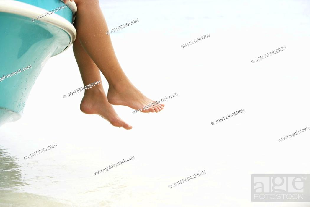 Stock Photo: South American woman dangling feet off of boat.