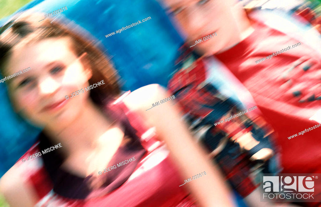 Stock Photo: A boy and a girl, a young couple or friends, are sitting on a blue inflatable deckchair in the garden, unsharp, blurred.