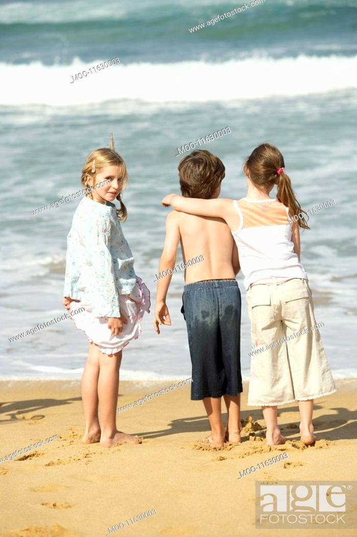 Stock Photo: Three children standing at water edge on beach back view.