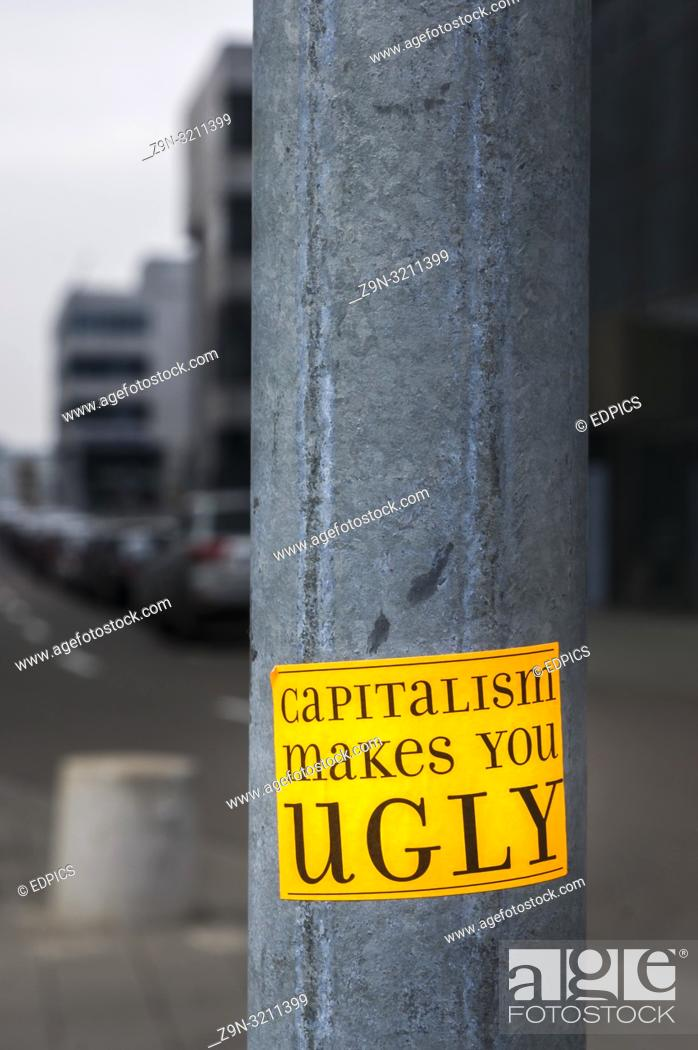 """Imagen: sticker on a lamp post in financial district with a text that reads: """"""""capitalism makes you ugly""""""""."""