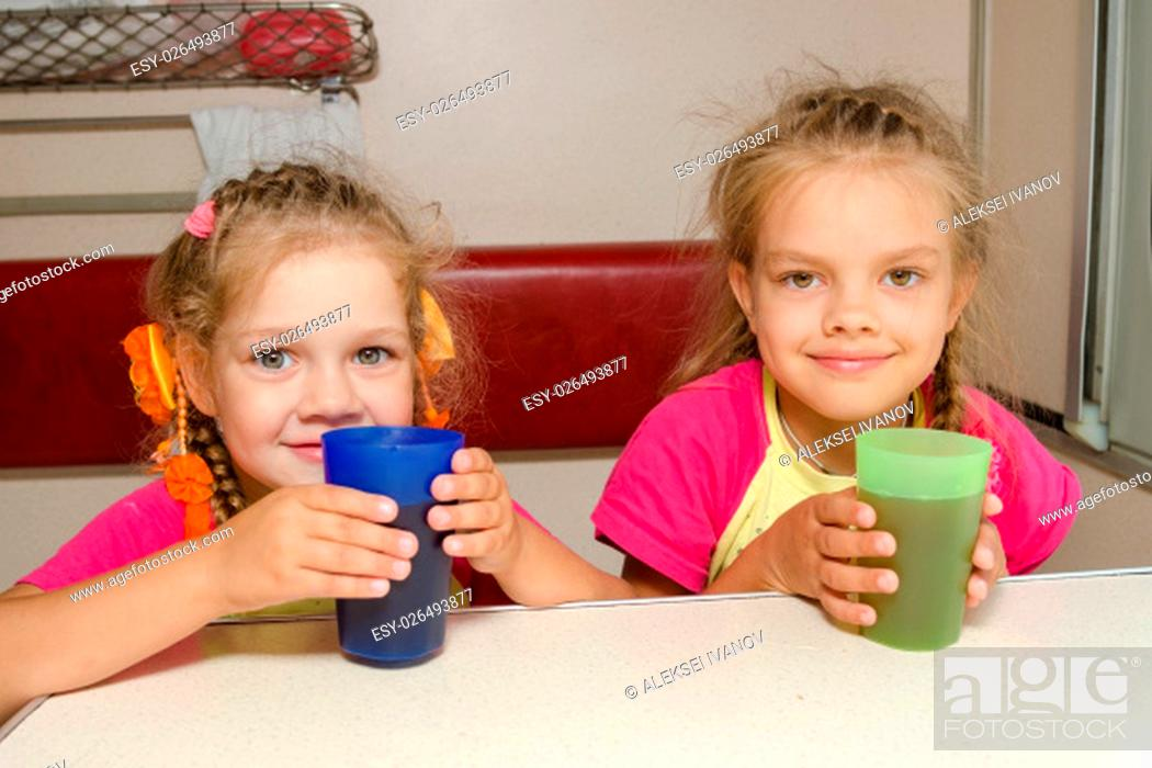 Stock Photo: Two girls sisters on the train sitting at the table on the lower place in the second-class compartment wagon with glasses in hand.