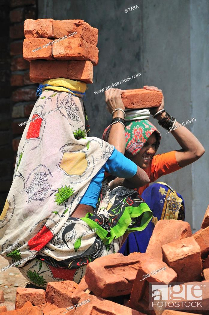 Stock Photo: Indian construction workers carry heavy brick.