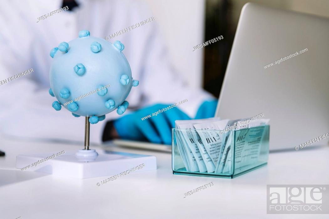 Stock Photo: Close-up of scientist using laptop next to up lateral flow test devices and corona virus model.