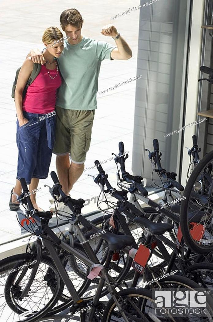 Stock Photo: Young couple looking at new bikes in bicycle shop window display, elevated view.