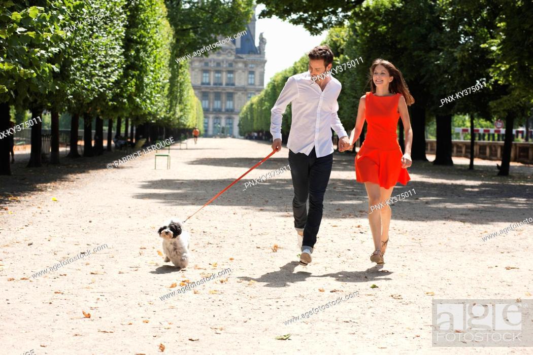 Stock Photo: Couple running in a garden with a puppy, Terrasse De l'Orangerie, Jardin des Tuileries, Paris, Ile-de-France, France.