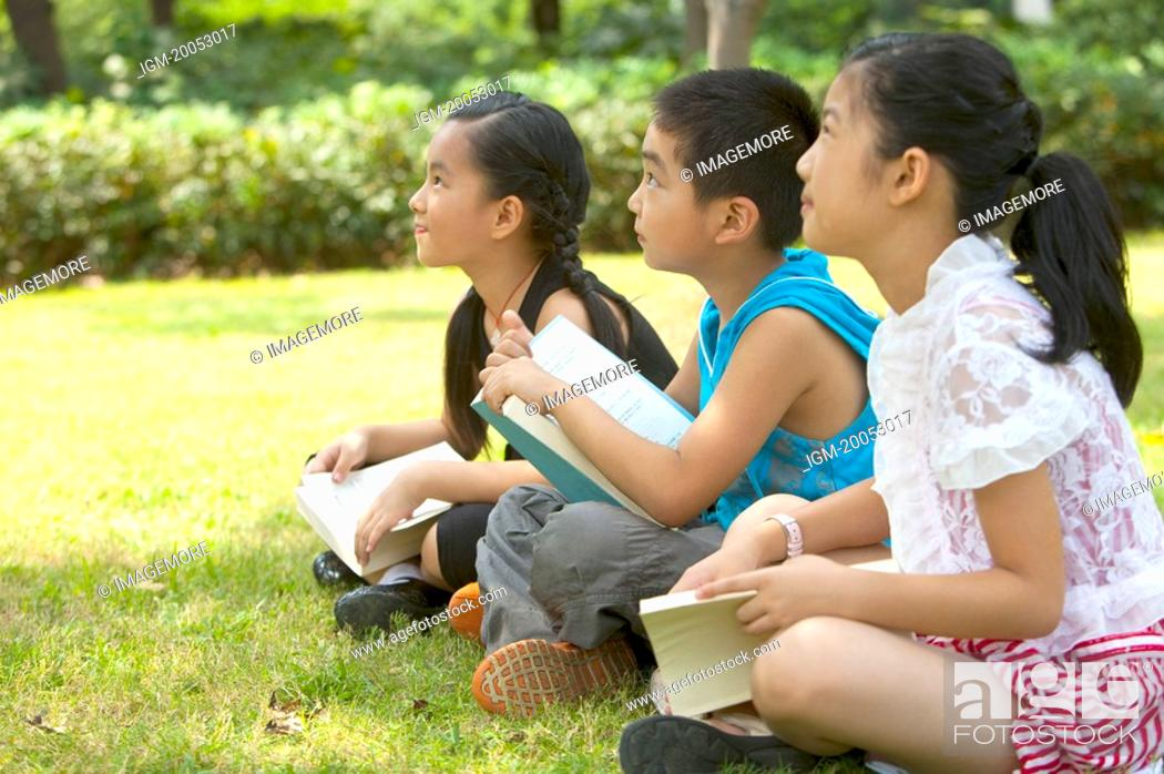 Stock Photo: Three children sitting on the lawn with books and listening together.