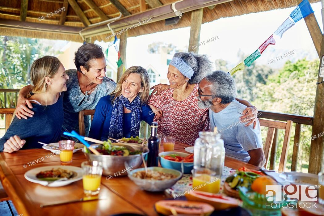 Stock Photo: Happy friends hugging, enjoying healthy meal in hut during yoga retreat.
