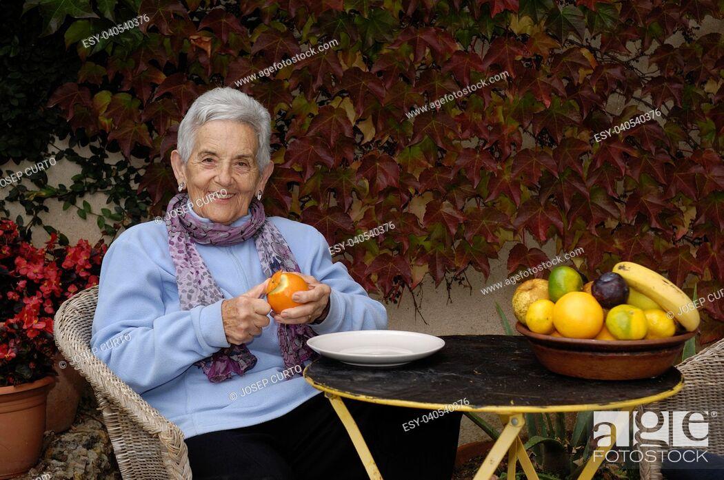 Stock Photo: senior woman with a orange fruit.
