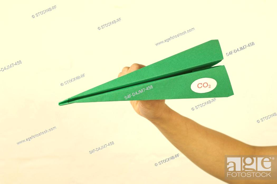 Stock Photo: Hand holding green paper plane with CO2 label.