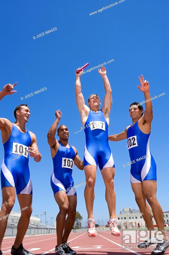 Stock Photo: Young male runners cheering after winning race.