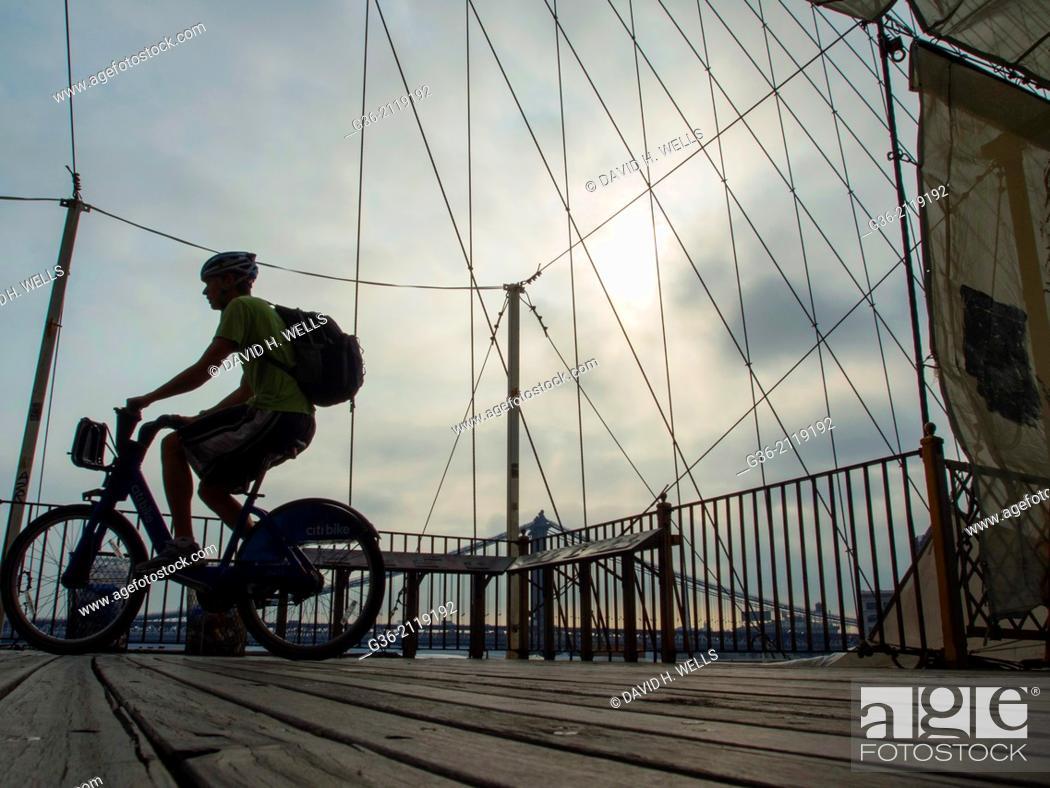 Stock Photo: Silhouette of man riding bicycle on Brooklyn Bridge, in New York, New York.