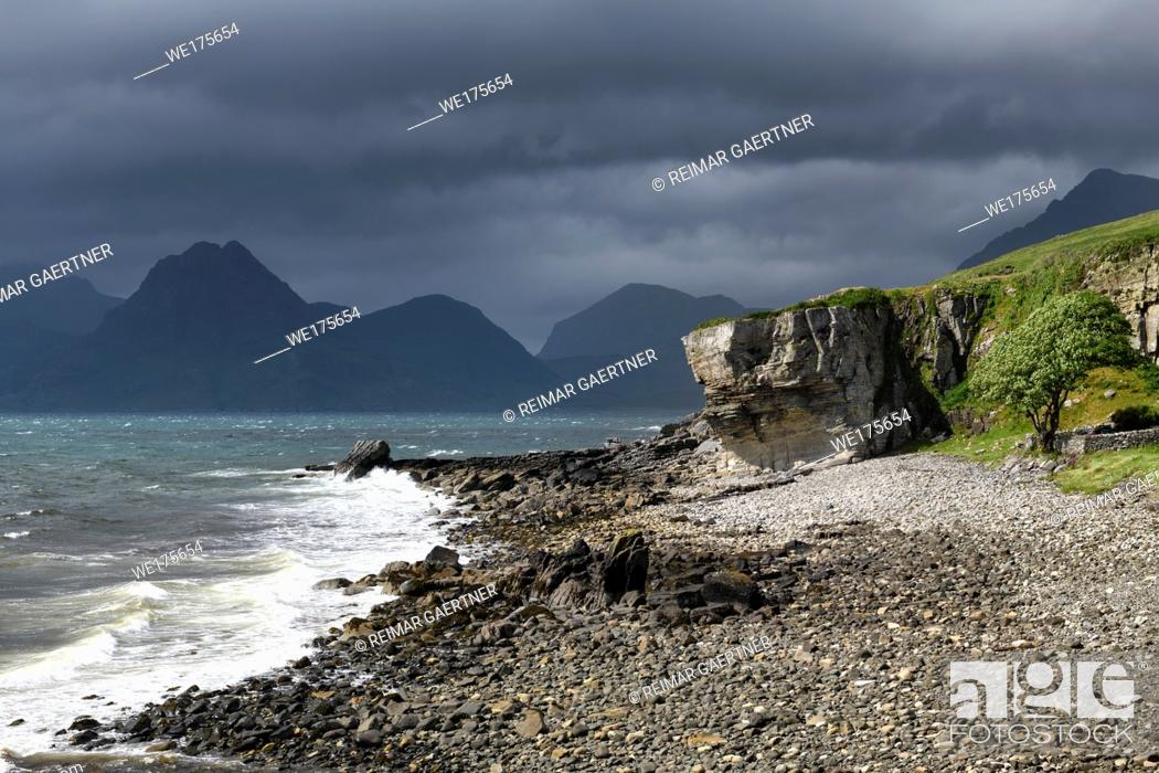 Stock Photo: Rocky shore at Port na Cullaidh harbour Elgol with Red Cuillin Mountains under clouds at Loch Scavaig Isle of Skye Scotland UK.