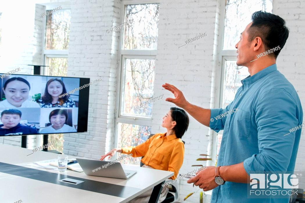 Stock Photo: Business men and women in the meeting room video meeting.