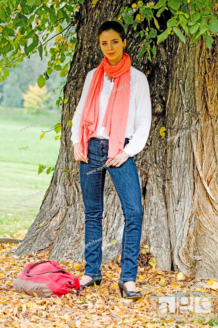 Stock Photo: Woman with red bag under large tree. Woman in white blouse and dark blue jeans with coral scarf stands under a large tree.