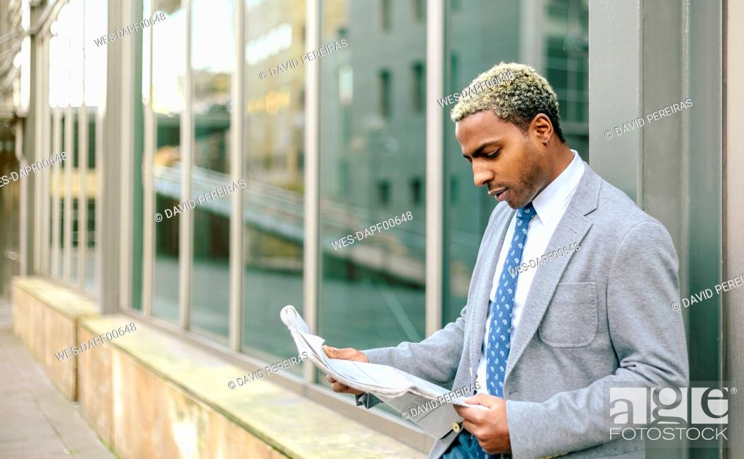 Stock Photo: Businessman leaning against wall, reading newspaper.