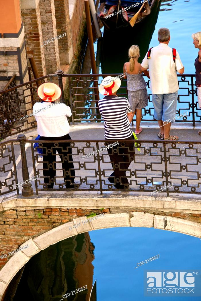 Stock Photo: Two gondoliers on a bridge waiting for tourists, with a gondola, Venice, Italy.