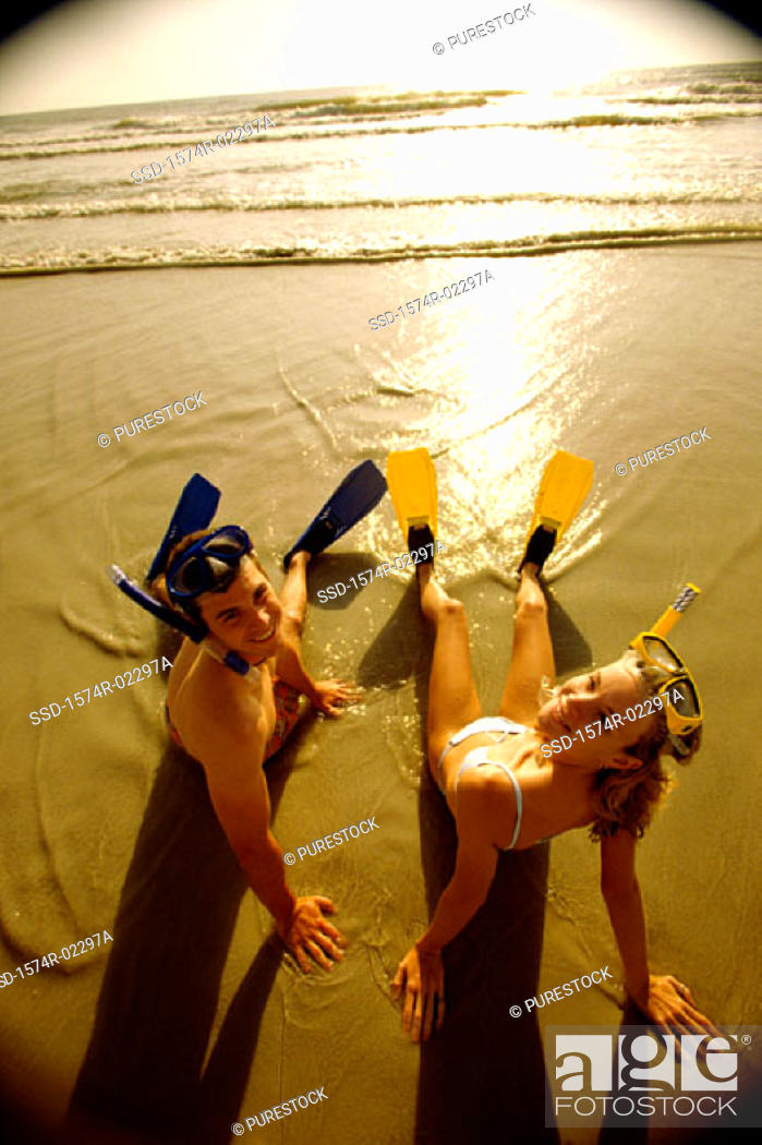 Stock Photo: High angle view of a teenage couple sitting on the beach wearing snorkels and flippers.