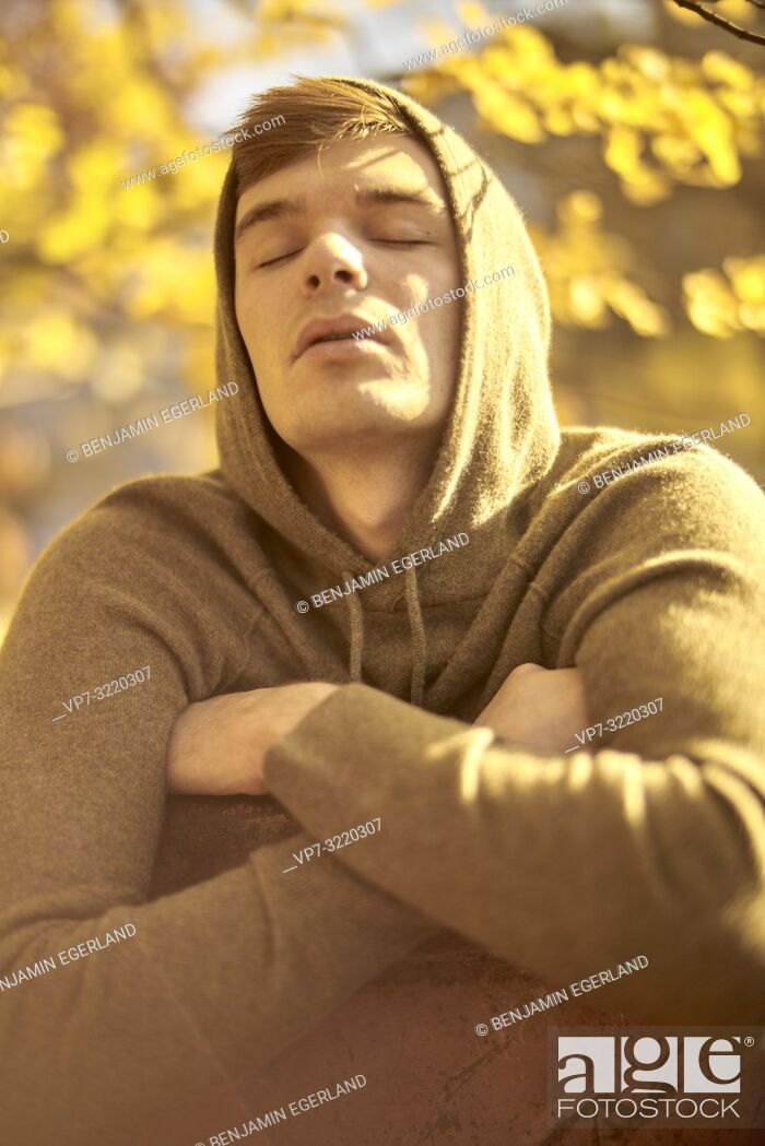 Stock Photo: Young emotional man with closed eyes outdoors in autumn, wearing hoody pullover, in Munich, Germany.