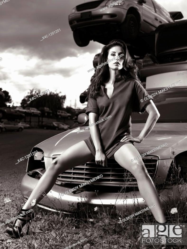 Stock Photo: Sexy young woman sitting on a hood of a wrecked car at a scrap yard.