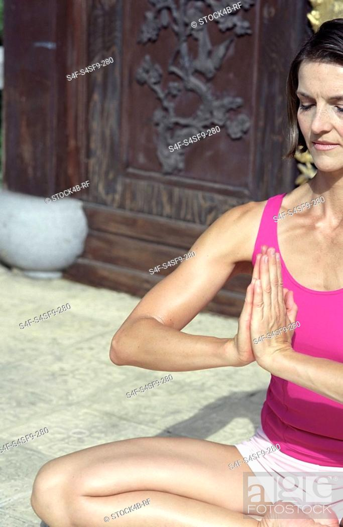 Stock Photo: Darkhaired Woman in a Buddha-Sit-Position - Yoga - Meditation - Posture.