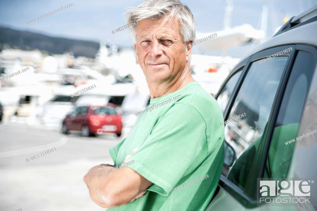 Stock Photo: Spain, Senior man leaning on car.