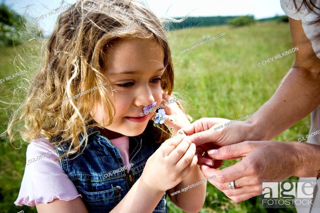 Stock Photo: Girl smelling flower.