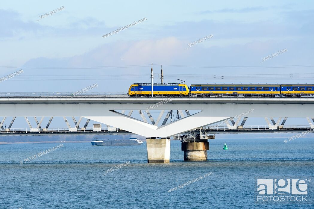 """Stock Photo: MOERDIJK, THE NETHERLANDS â. """" JANUARY 29: Train rides on the railway bridge over the Hollands Diep in Holland on January 29, 2017."""