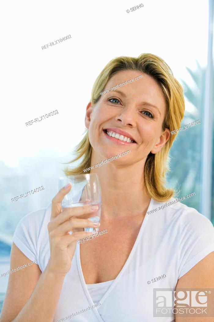 Stock Photo: Mature woman smiling and holding glass of water.
