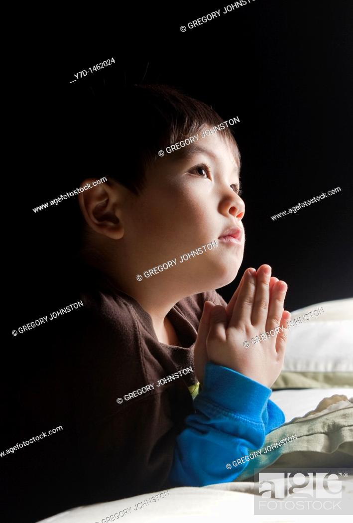 Stock Photo: A young boy says his prayers just before his bedtime.