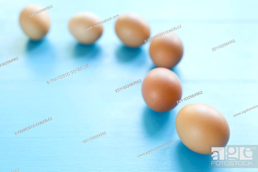 Photo de stock: several eggs isolated on a blue background.