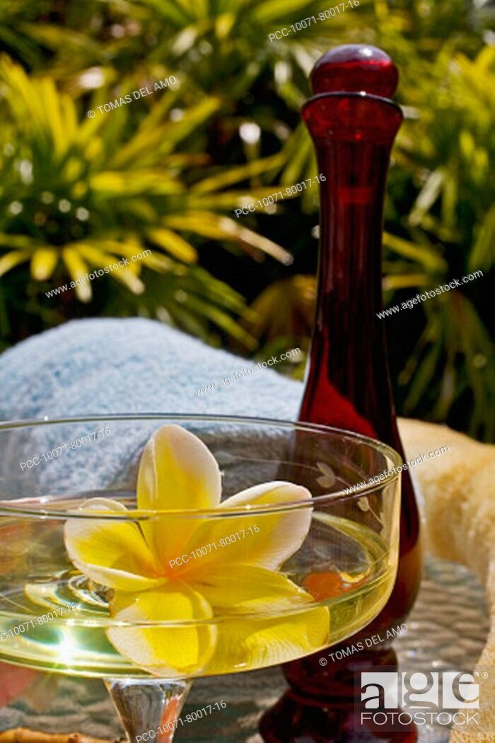Stock Photo: Spa elements, yellow plumeria floating in glass, with glass bottle, loofah and towel.