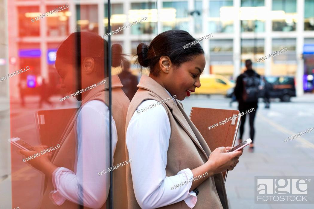 Stock Photo: Smiling businesswoman leaning against glass pane using cell phone.